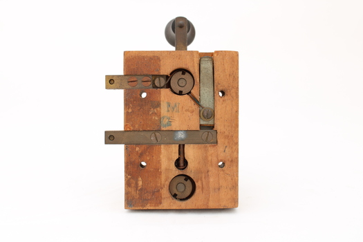 Metal device mounted on block of wood with handle that moves up and down via a spring.