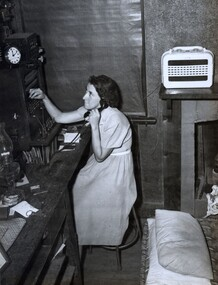 Young woman sitting on chair holding a telephone receiver to her ear while plugging a cord into a switchboard; pillows in the foreground.