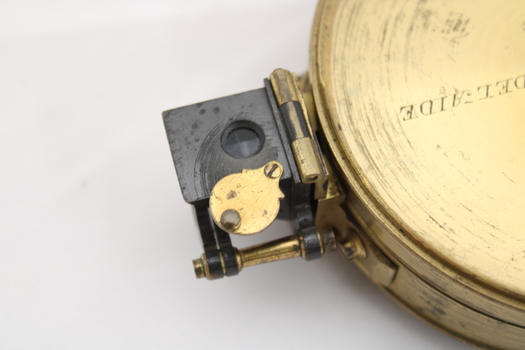 Gold coloured metal compass case with engraved lid; compass face is green printed paper with glass top.