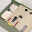 Green and cream box with black levers and removable plastic cartridge housing magnetic tape.