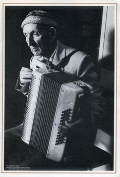 Elderly man holds a piano accordian