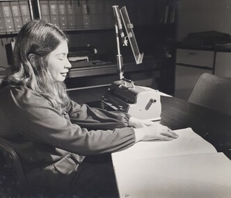 Woman reading Braille next to a Perkins