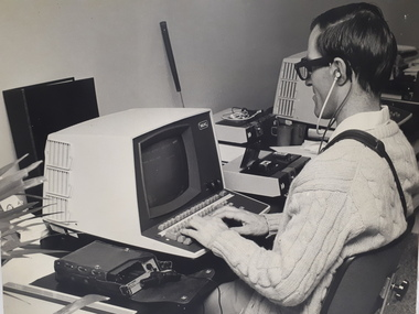 Man wearing a Sonic Guide types on a computer with an Opticon beside him