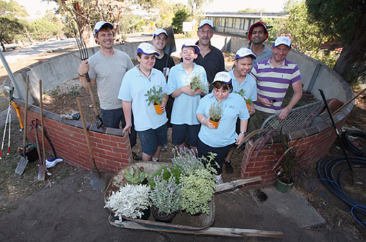 Five adults stand behind school children holding plants.