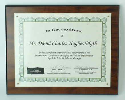 Paper certificate laminated on to wooden board.