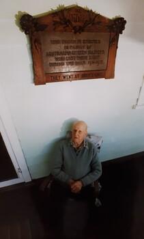 Elderly man sits beneath wooden plaque on verandah.