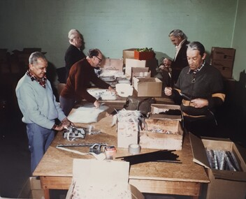 Five men standing around a table packing unknown materials into plastic pockets