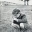Photograph of small boy kneeling in grass below Burwood building, holding flowers