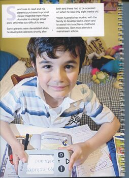 A young boy, Sam, holds a pocket magnifier over a book in his bedroom