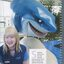 Stephanie Bradbury sitting next to a shark statue at the swimming complex she works at