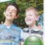 Two schoolboys, James and Riley, put an arm around each other's shoulders and turn towards camera