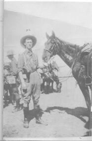 soldier standing with his horse.