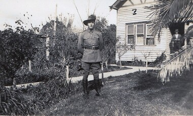 Soldier standing in front of farmhouse