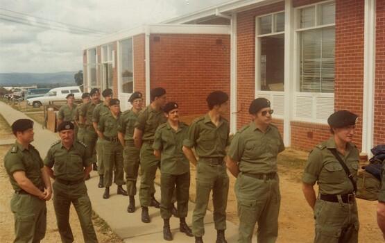 Line of soldiers beside brick building