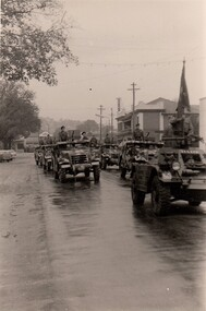 Army vehicles in street on rainy day.