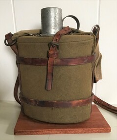 metal container wrapped in felt and held in leather straps, small metal cup in top.