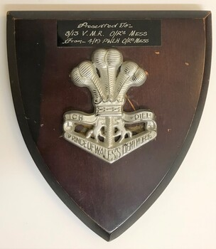 A wooden shield with a silver badge attached to it.