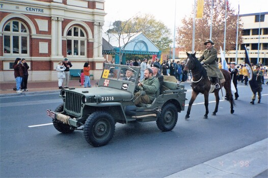 Jeep followed by soldier on a horse