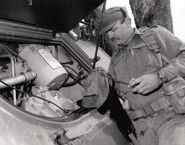 Soldier checks oil in vehicle