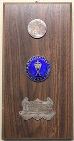 Stained board with badges and inscribed panel fixed to it.