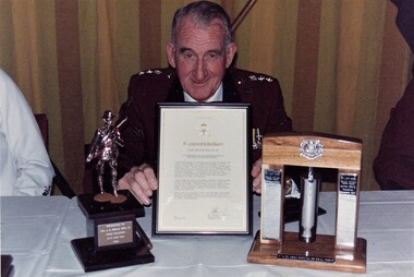 Army officer at table with 3 gifts.