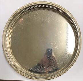 Large circular silver tray with engraving at centre.