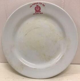 Crockery plate with monogram on edge.