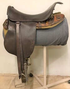 Leather riding saddle placed on a metal stand