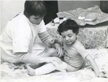 A Royal District Nursing Service Sister attending to a child's wounds