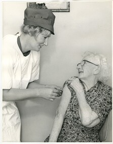 A Melbourne District Nursing Service (MDNS) Sister administering an injection to an elderly lady