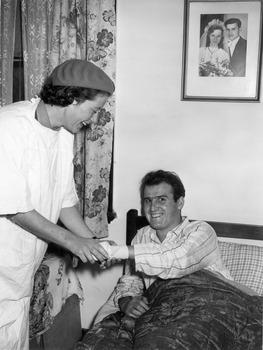 Melbourne District Nursing Service (MDNS) Sister bandaging a gentleman's wrist