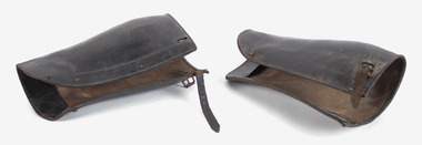 A pair of brown leather leg-gaters, lying on their side on a white back-ground. There is a buckle and strap to fasten at the top.