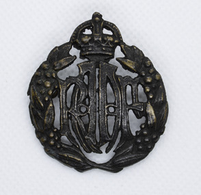 Blackened brass badge with crown on top and leaf crest either side of the letters RAAF in centre
