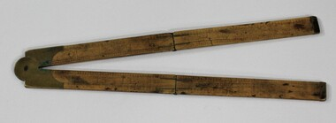 Wooden fold out carpenter ruler with bendable brass hinges and imperial measurements engraved into the wood.