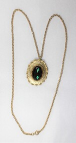Front of a gold toned metal cable chain necklace with an oval pendant and a faceted green/brown glass setting.
