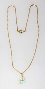 Front of a necklace with a gold toned metal chain and a small blue bird pendant and a small faux pearl.