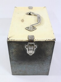 One end of a rectangular grey metal railways lunch box with a cream coloured lid secured with metal clips and a metal handle on the lid.