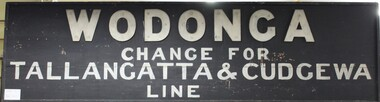 Painted wooden sign from the Wodonga train station with the directions for changing to the Tallangatta and Cudgewa train line in light coloured paint on a black background.