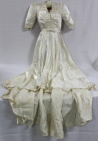 A floor length white satin wedding dress with structured sleeves and studded diamantes