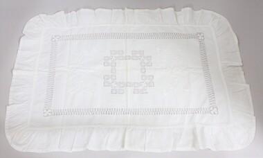 A handmade white pillow sham with needlework