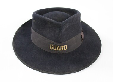 Dark blue/grey felt Victorian Railways hat with the word 'GUARD' in gold on the front of a faded brown band.