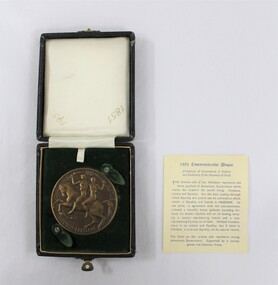 Circular bronze medal depicting a man and a woman riding a horse, in a small presentation box with a dark green velvet insert for the medal in the lower part and a light coloured textile printed with the dates 1851 and 1951 in the lid. Text on paper with a description of the medal next to the case.
