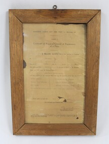 Wooden frame around a deteriorated paper certificate for the official registration of the Dunstan's Drying Kiln company in 1954 with a plastic layer covering the certificate.