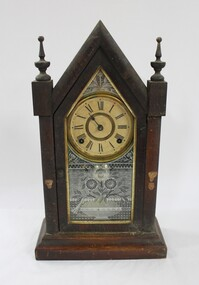 A gothic style wooden clock with gold and white embellishments, and Roman Numeral numbering on the clock face