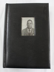 A black photographic album with a photograph of a man inserted into the front cover