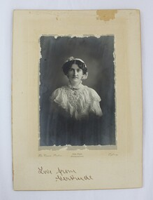 A black and white mounted photograph of a woman in a white, frilled dress