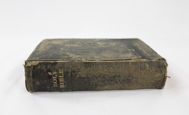 A black cloth bible with Holy Bible embossed on the spine in gold