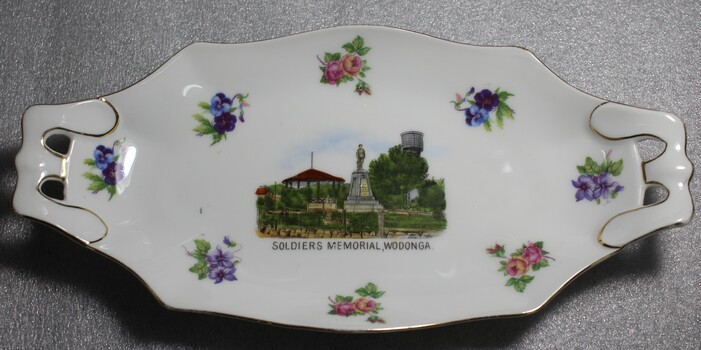 An oblong china dish. White with floral emblems and image of Soldiers Memorial, Wodonga