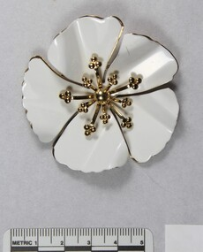 White and gold-toned metal flower-shaped brooch from the Sarah Coventry Pty. Ltd. jewellery range with a 5 cm  black and white scale.