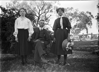 Stan Young seated between two of his sisters who are standing beside him. Trees and a wooden fence are in the background.